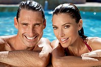 Close up portrait of a beautiful happy man and woman couple resting on their hands at the side of a sun bathed swimming pool smiling with perfect teet...