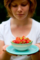 Girl holding a bowl of beautiful fresh strawberries outdoors on a summer day