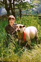 Junge Frau auf Wiese mit Schaf