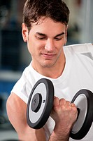 portrait of young man doing weightlifting in gym
