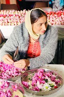 Asian woman making garlands for the Baisakhi festival,