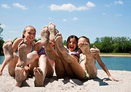 Girlfriends sitting on the beach of a lake with their sand-covered feet stretched to the front