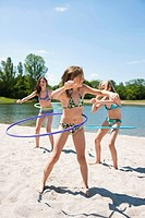 Girls playing with hula-hoops on the beach of a lake