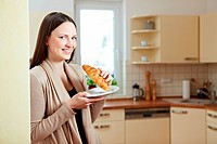 Attractive woman standing with croissant in a kitchen