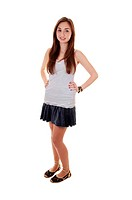 An beautiful teenager standing in a short skirt and gray t_shirt, withher long brunette hair, over white background.
