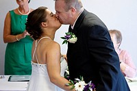 Bride who has cerebral palsy, kissing groom at wedding ceremony