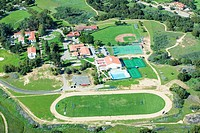 Springtime aerial view of Villanova Prep school with track, pool, baseball diamond, tennis courts and campus in view, Ojai, CA