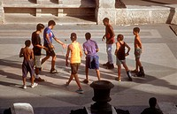 Group of teenage youths playing with ball on the Paseo Jose Marti was Paseo del Prado in Havana, Cuba,