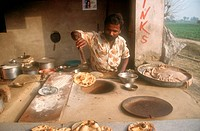 Man making nan bread in Tandoori oven,