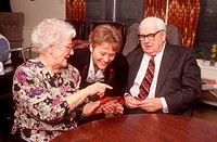 Elderly man and woman playing game of cards at day centre with carer watching