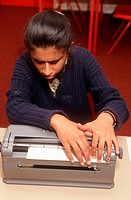 Young girl with visual impairment reading Braille from Braille machine,