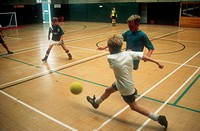 Group of young children playing game of football in sports hall