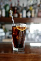 Glass of coke with a lemon and straw on bar top