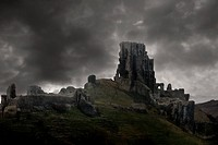 The ruins of Corfe Castle in Dorest England under a very dramatic sky.