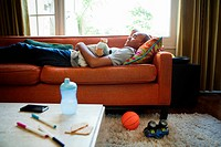 Man lying on sofa asleep with toys