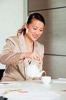 Businesswoman pouring tea