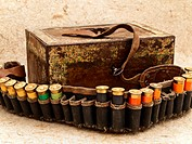 Photo of old ammunition belt with shells and vintage rusty chest against beige background
