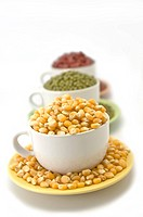 Three different dry grains in white cups and matching colored saucers: red adzuki beans, golden corn and green mung beans.