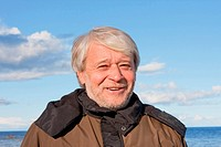Portrait of mature smiling man with grey hair at the Baltic sea in autumn day.