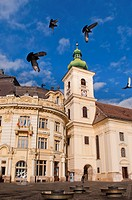 main square and catholic church historical arhitecture in Sibiu Romania with pigeons flying in the air
