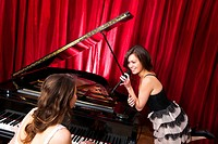 Two women singing a duet with a concert piano