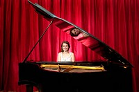 Young girl, smiling whilst playing on a grand piano in front of the red curtains on stage