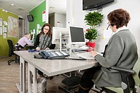 Several women working at the helpdesk of a hospital, answering questions from patients over the phone