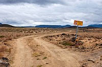 Warning sign adjacent to a winding dirt road in the barren landscape and tundra of Iceland