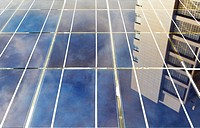 Building and sky reflected in modern high efficiency photovoltaic panels