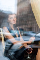 Beautiful woman is sitting in restaurant behind the window