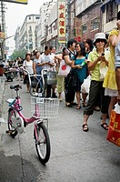 People waiting on a queue to buy cookies, Nanjing Road, Shanghai, China.