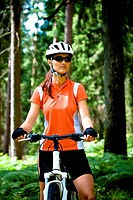 cycling woman in front of forest