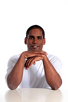 An attractive dark_skinned sitting at a table. All on white background.