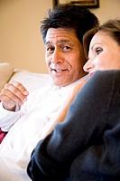 Mature Hispanic man sitting on sofa, affectionate wife leaning on shoulder
