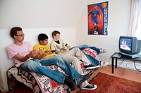Groups of youths on sofa watching television