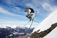 Skier jumping off snowy slope