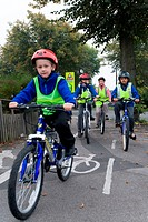 Group of children cycling home from school on a designated cycle path accompanied by a parent