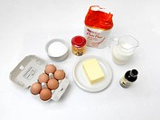 Ingredients _ Jug Of Milk, Plain Flour, Vanilla Extract, Bowl Of Sugar, Butter, Eggs And Baking Soda