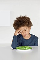 Young boy sulking infront of a plate of peas
