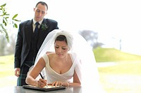 Newlywed couple signing marriage license