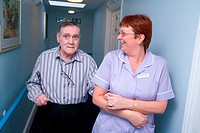 Care Assistant leading a man with Alzheimer's Disease down the corridor of a nursing home