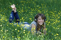 Woman listening to headphones in grass