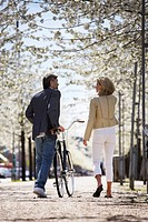 Couple walking bicycle in park