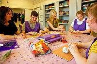 Day Service Assistants working with a Group of Day Service users with learning disabilities in an arts and crafts session,
