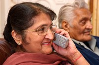 Elderly south Asian couple, woman on phone