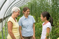 Grandmother and daughter chatting with granddaughter inside greenhouse