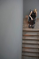 Woman in wheelchair at top of stairs