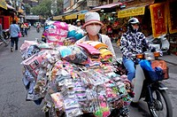 Woman street vendor pushing her bike overloaded with household linen, Hanoi, North Vietnam