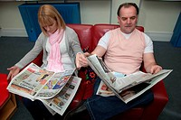 Couple reading newspapers in a library