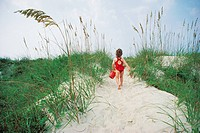 Girl walking towards beach